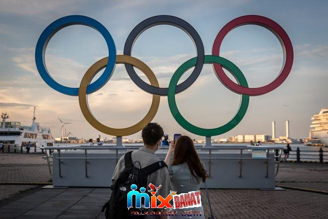 People take photographs of Olympic rings.
